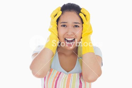 Distressed woman wearing apron and rubber gloves
