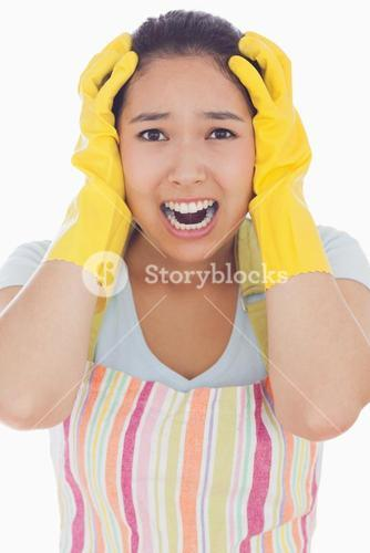 Stressed woman wearing rubber gloves and apron