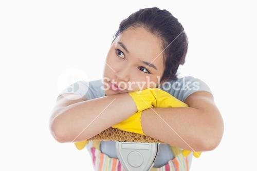 Troubled woman leaning on a mop