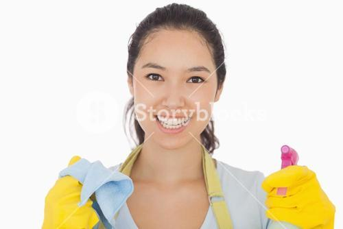 Smiling woman with cloth and spray bottle