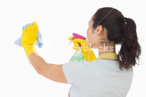 Woman spraying and wiping in rubber gloves