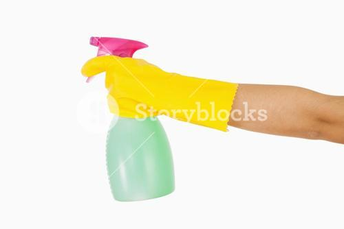 Woman in yellow rubber gloves holding window cleaner