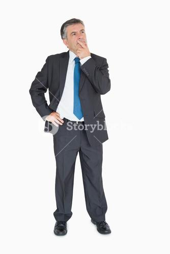 Businessman thinking with one hand on hip
