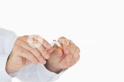 Male hands breaking a cigarette