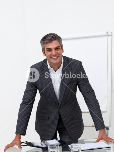 Assertive businessman leaning on a conference table