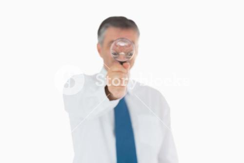 Businessman behind magnifying glass