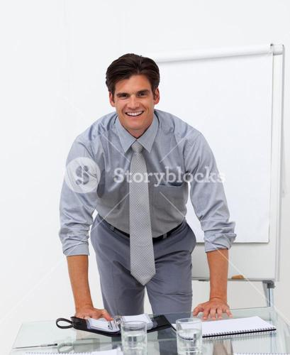 Cheerful businessman leaning on a conference table