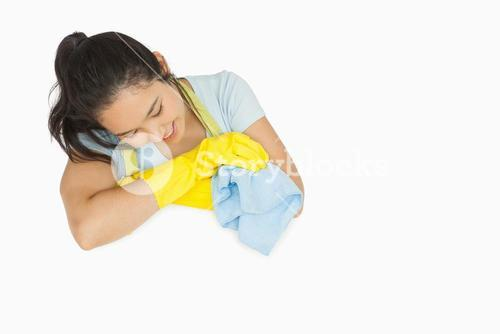 Smiling woman in rubber gloves looking at white surface