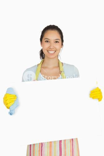 Woman in apron and rubber gloves holding white surface