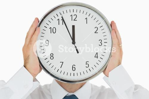 Man hiding face with a clock