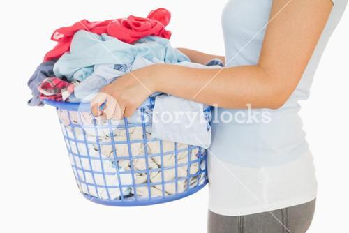 Woman holding a basket overflowing of laundry