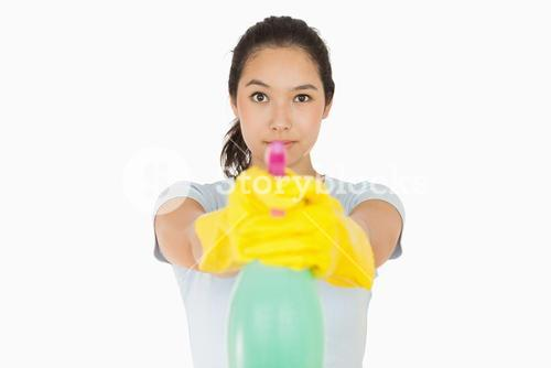 Woman pointing a spray bottle at the camera