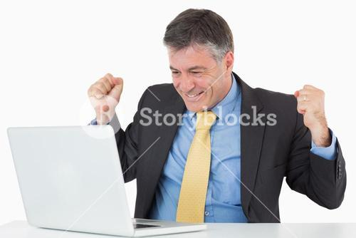 Very happy man sitting at his desk with laptop