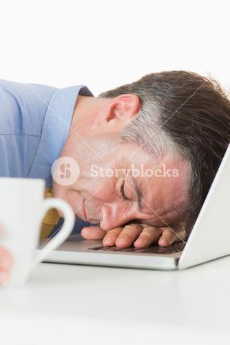 Overworked man sleeping on his laptop while holding coffee