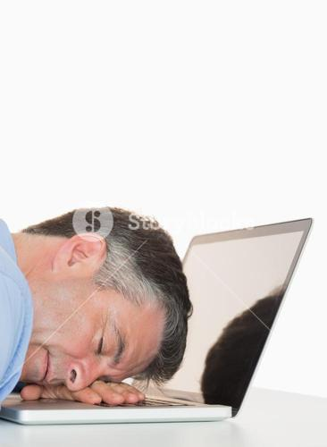 Exhausted man sleeping on his laptop