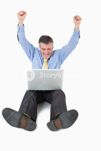 Succesful man on the floor with his laptop