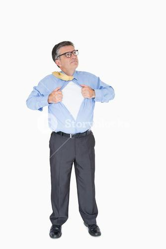 Concentrated man with glasses is pulling his shirt with his hands