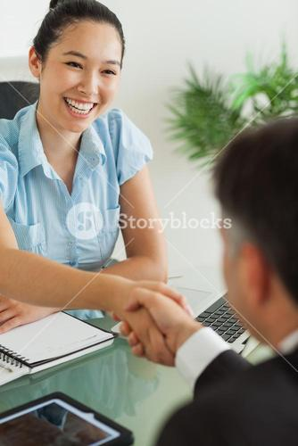 Smiling businesswoman shaking mans hand