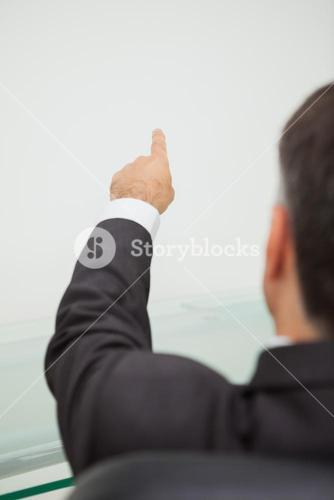 Businessman pointing to a white wall