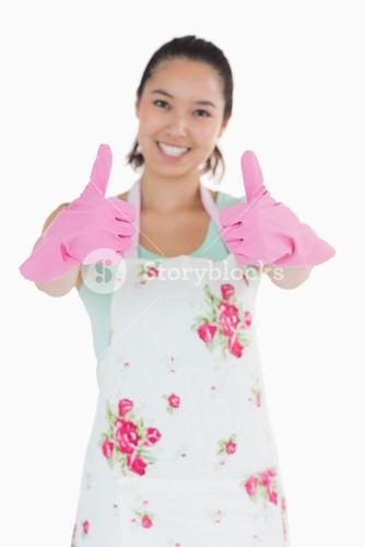Happy woman in rubber gloves giving thumbs up