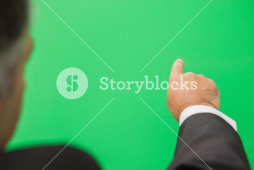 Businessman pointing to green copy space