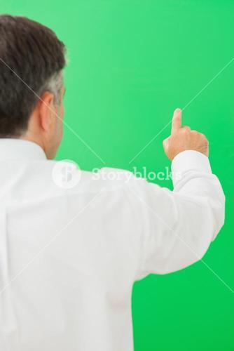 Businessman pointing to chroma key