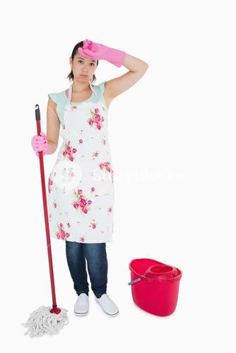 Discouraged woman cleaning floor