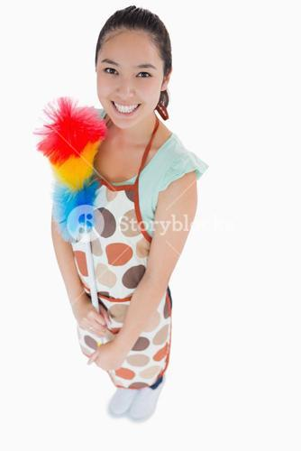 Happy woman holding duster