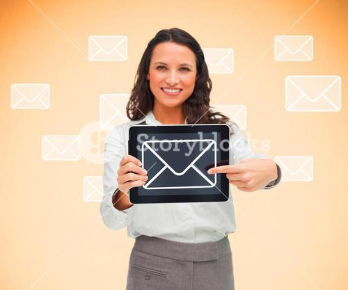 Woman standing smiling while holding a tablet pc and pointing to mail symbol