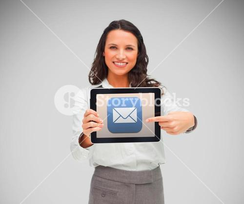 Businesswoman smiling while holding a tablet computer and pointing to mail symbol