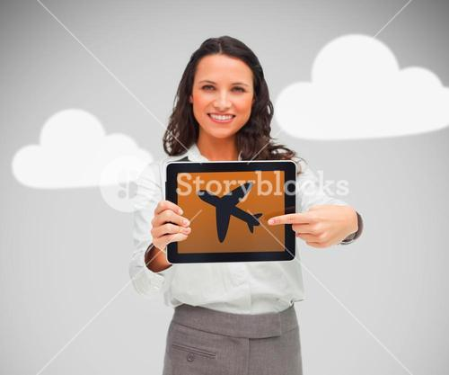 Businesswoman pointing at plane symbol on tablet pc