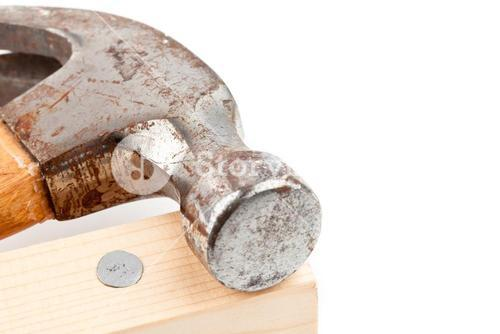 Nail in a plank and a hammer lying on it