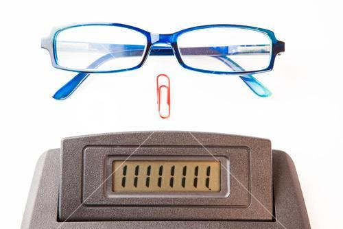 Sector of calculator display with glasses and paper clip