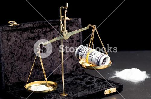 Weighing scales with dollars and drugs