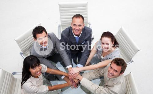 Smiling business team with hands together