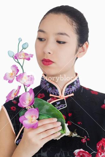 Woman in kimono holding orchid