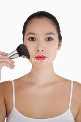 Woman using powder brush