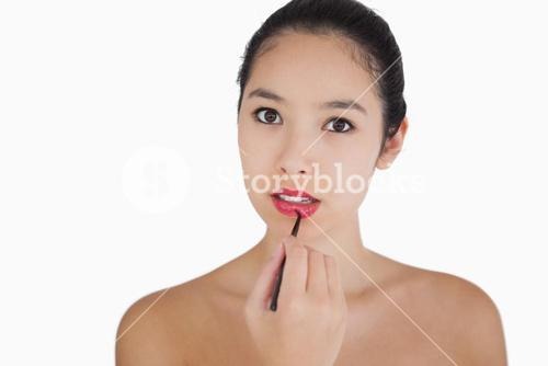 Woman putting on lipstick with a brush
