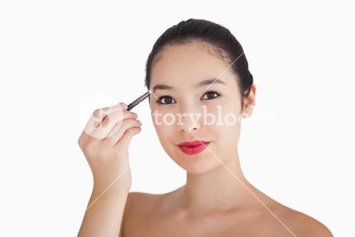 Smiling woman filling in eyebrows