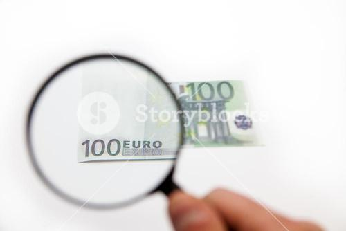 Hand holding magnifying glass over euro note
