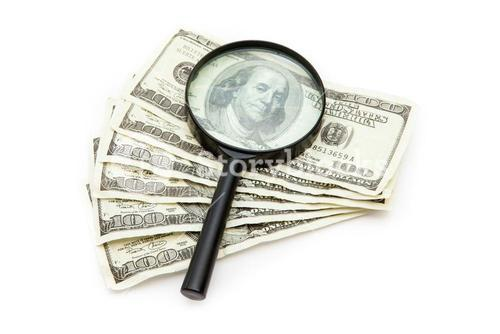 Magnifying glass resting on dollars