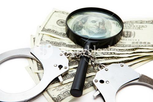 Handcuffs dollars and a magnifying glass