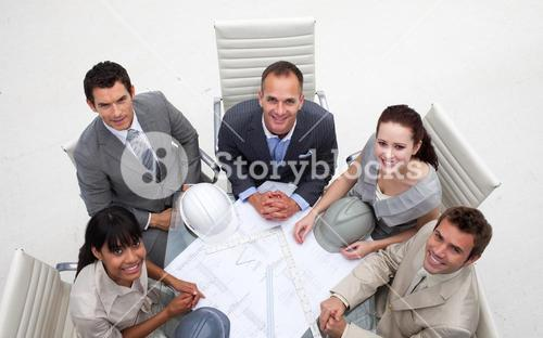 High angle of engineers working with plans
