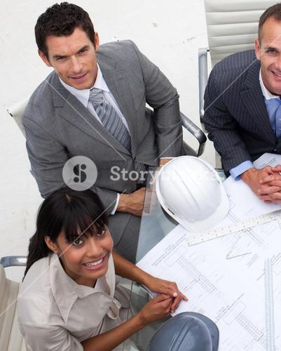 High angle of architects working with blueprints