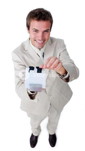 Smiling businessman holding a book at the camera