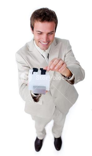 Positive businessman holding a book at the camera