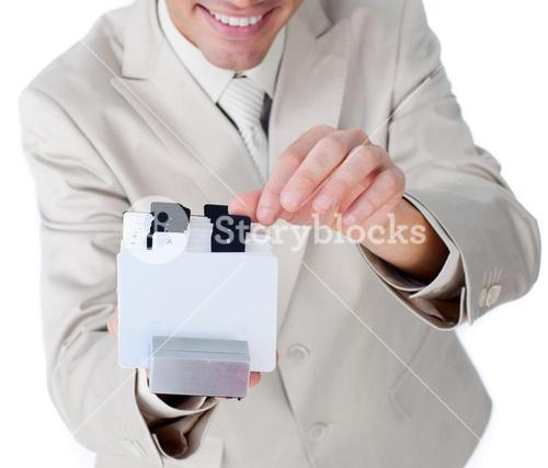 Attractive businessman holding a book at the camera