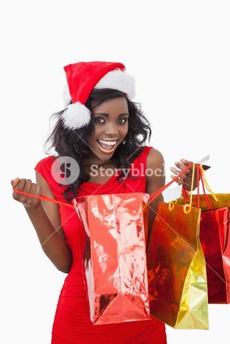 Woman holding bags while smiling