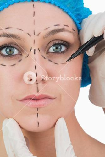 Doctor drawing on womans face for face lift