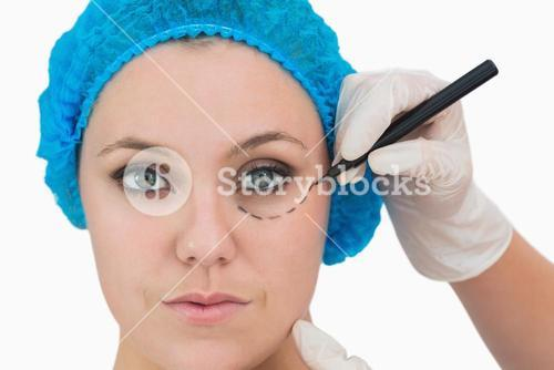 Plastic surgeon writing on womans face